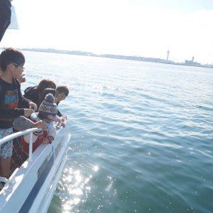 笑顔で東京湾に散骨を行う家族