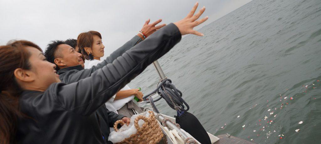 散骨セレモニーとして故人に捧げる花びらを東京湾に撒く男女
