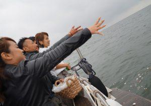 クルーザーの後方デッキから東京湾に花びらをまく4名の男女
