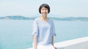 海沿いの堤防に腰掛けてほほ笑む美しい妙齢の女性