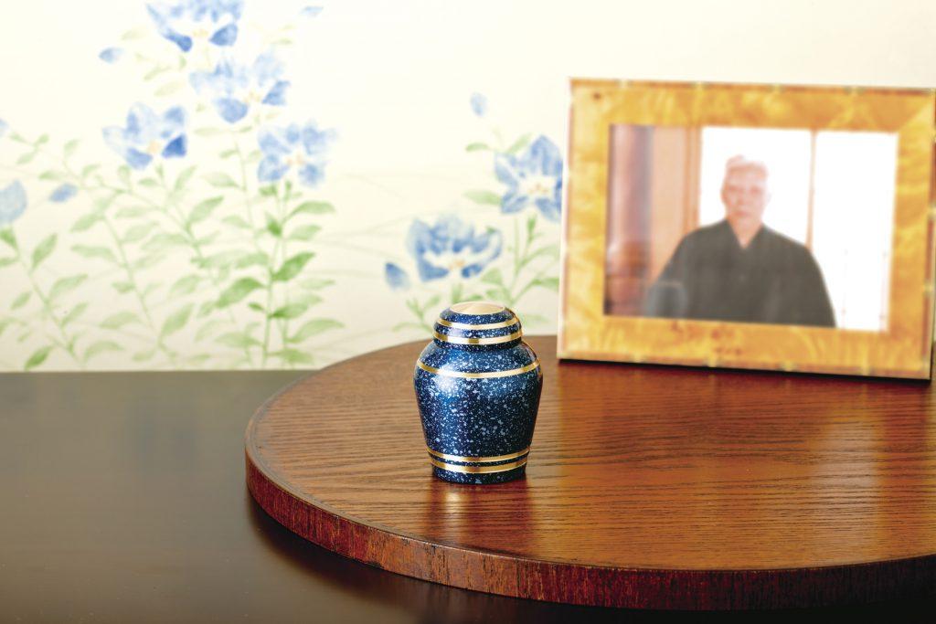 卓上に置かれた遺影と青い小型の骨壺