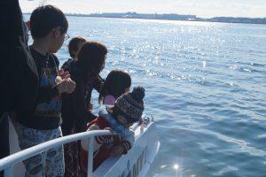 散骨セレモニーとして東京湾に花びらを撒く子供たち