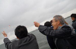 散骨セレモニーで東京湾に花びらを海に撒く遺族