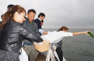散骨セレモニーで東京湾に献酒をする女性と花びらを撒く女性
