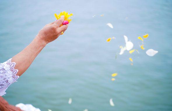花びらを海に撒く老婆の手