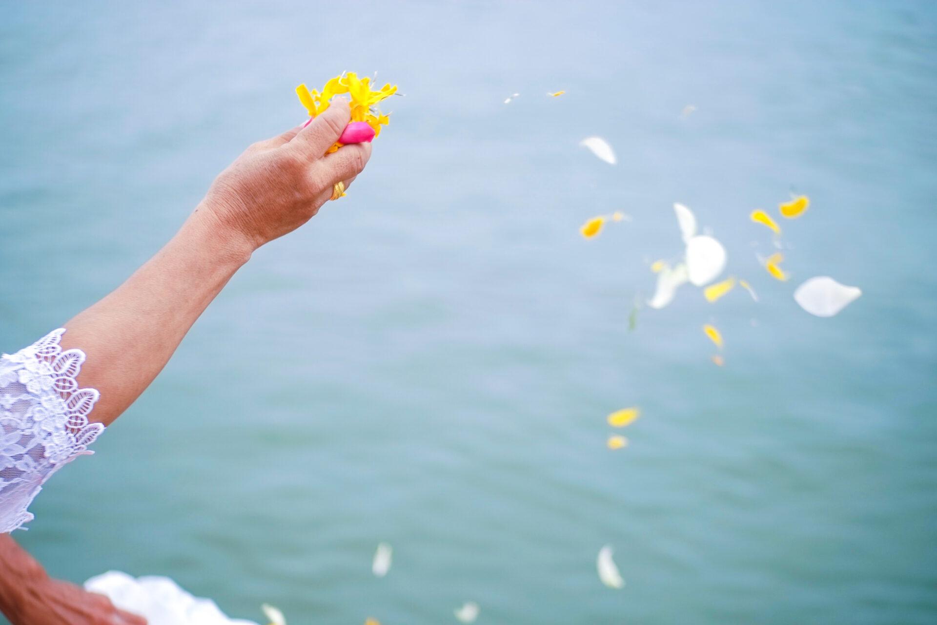 散骨セレモニーで花びらを海に撒く老婆の手