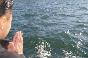 東京湾に黙とうを捧げる若い男性