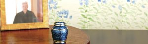 卓上に置かれた遺影と小型の青い骨壺