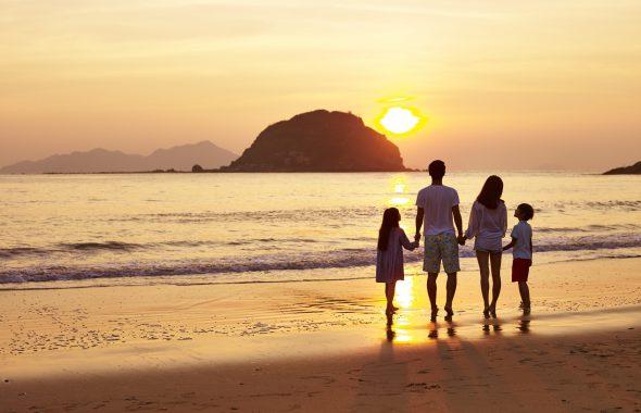 夕焼けの海岸に立つ4名の親子