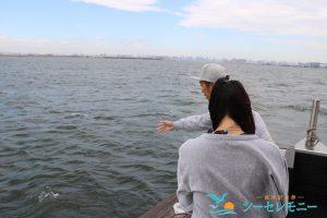 東京湾に散骨する若い男性と見守る女性