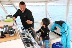 操船体験をする子供と見守る船長