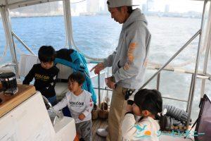 操船体験をする子供たちと見守る大人