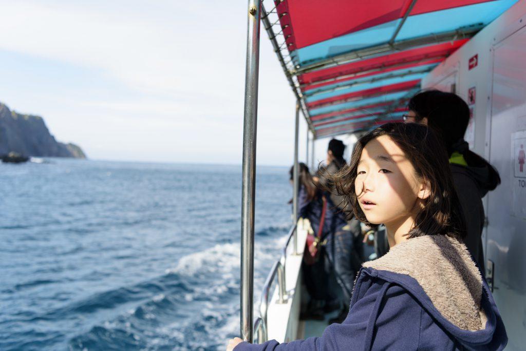 船のデッキから海を眺める人たち