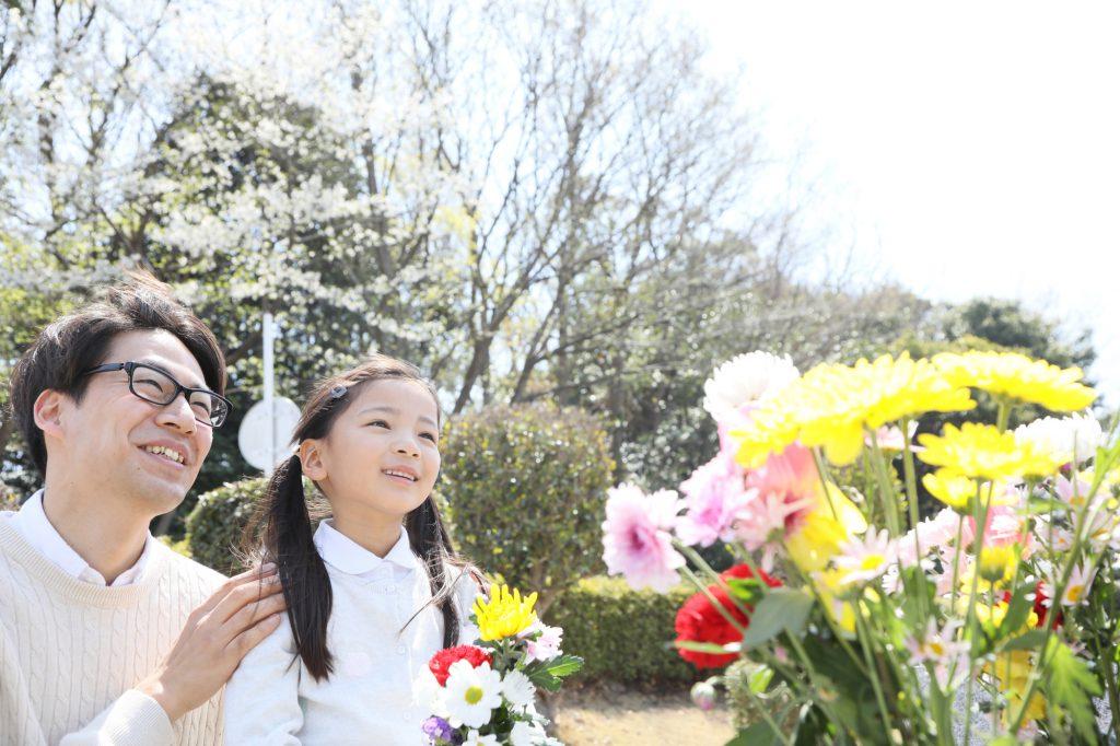 花を前にほほえむ親子