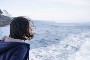 船から海を見つめる女の子
