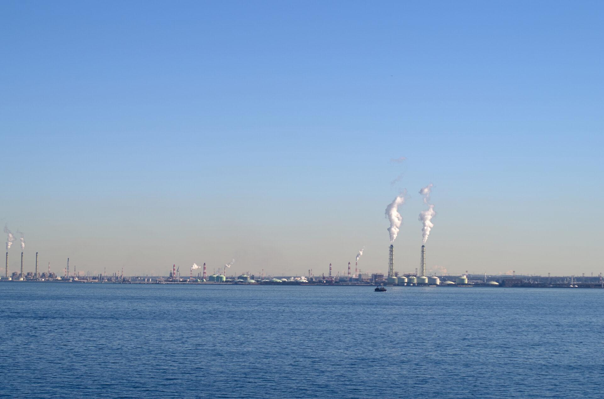 広い海の向こうに工場の煙突が見える