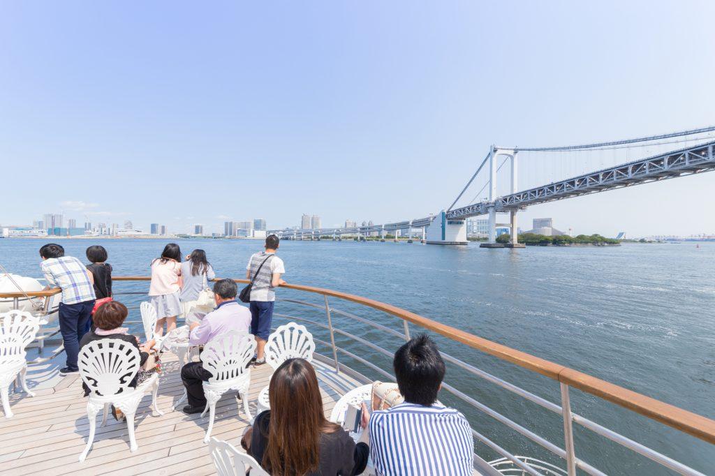 船のデッキから穏やかな海を眺める人たち