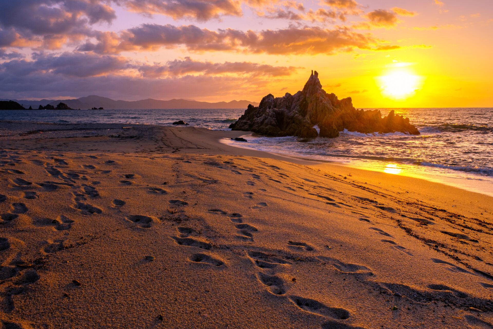 砂浜と夕焼け、そして浅瀬の岩場