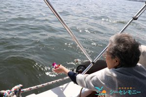 散骨セレモニーで東京湾に献花する高齢の女性