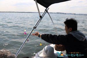 散骨セレモニーで東京湾に献花する男性