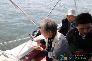 東京湾に散骨する高齢の女性と見守る家族