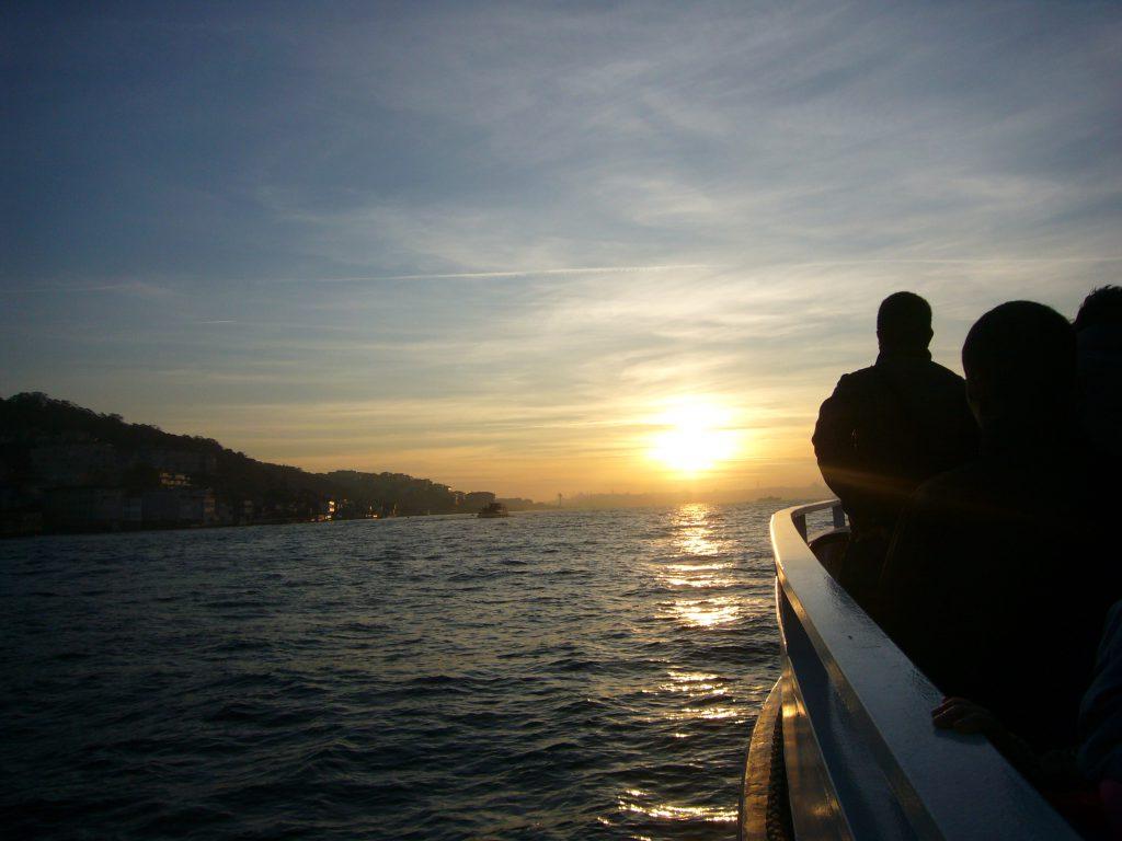 船のデッキにいる人と夕日