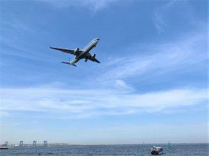 海上から見上げた着陸態勢に入った飛行機
