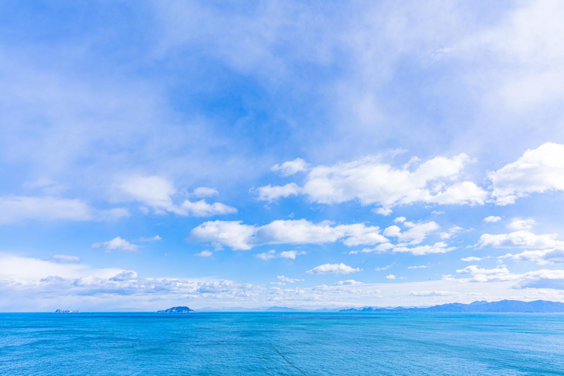 青空に雲がかかり、広大な海が見る