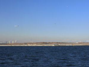 快晴の東京湾と青空を飛ぶ飛行機