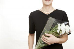 喪服を着て白い花を持つ女性