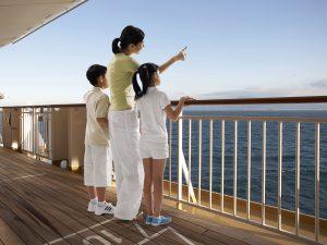 船から海を見ている親子3人