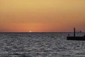 夕日が水平線の向こうへ沈む様子