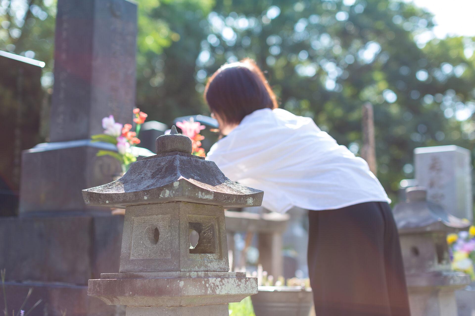 女性がお墓で供養している