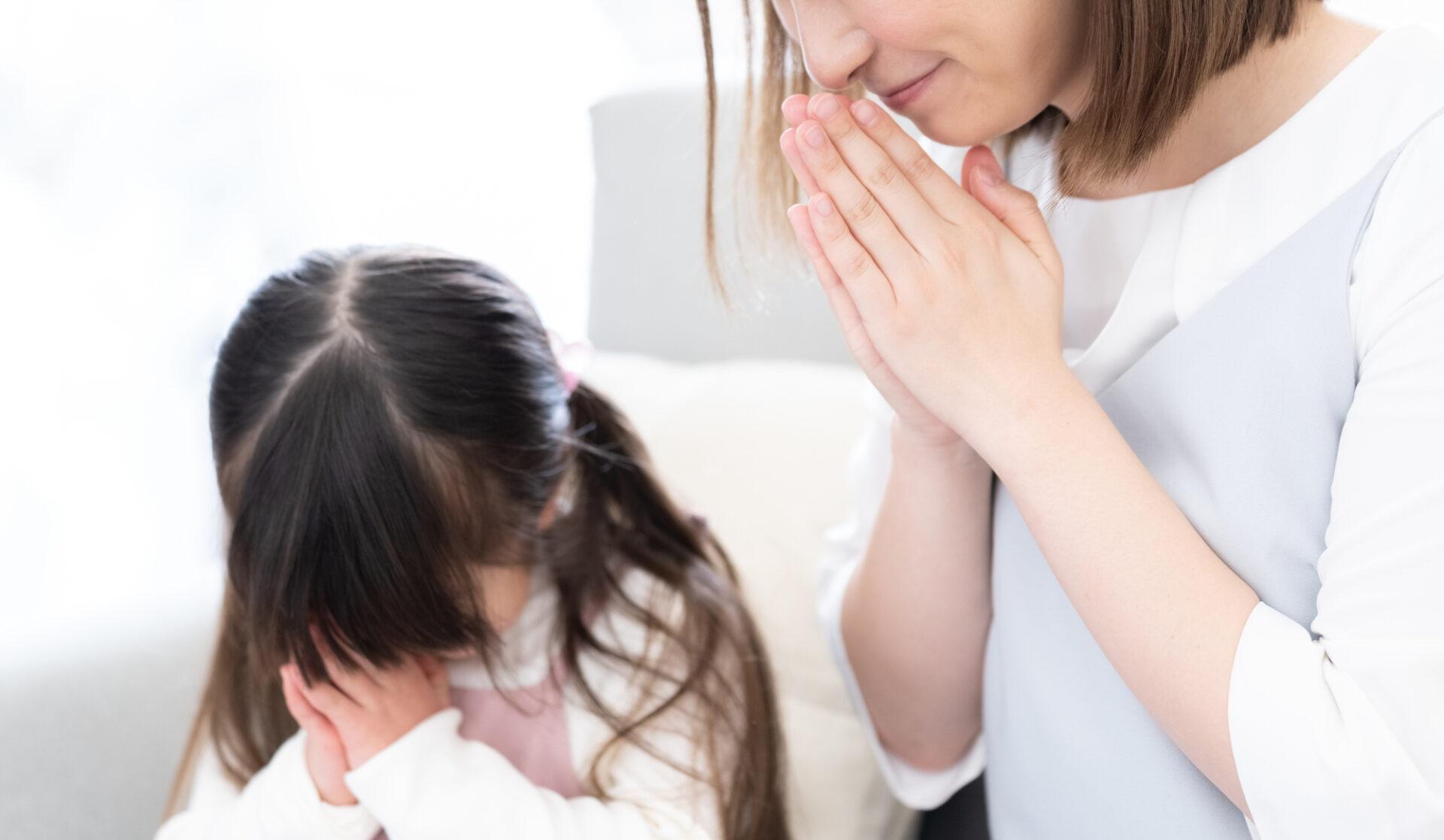 子どもと女性が手を合わせて黙祷