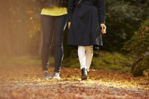 落ち葉の上を並んで歩く二人の女性