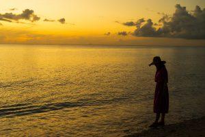 夕暮れ時の波打ち際に立つ女性