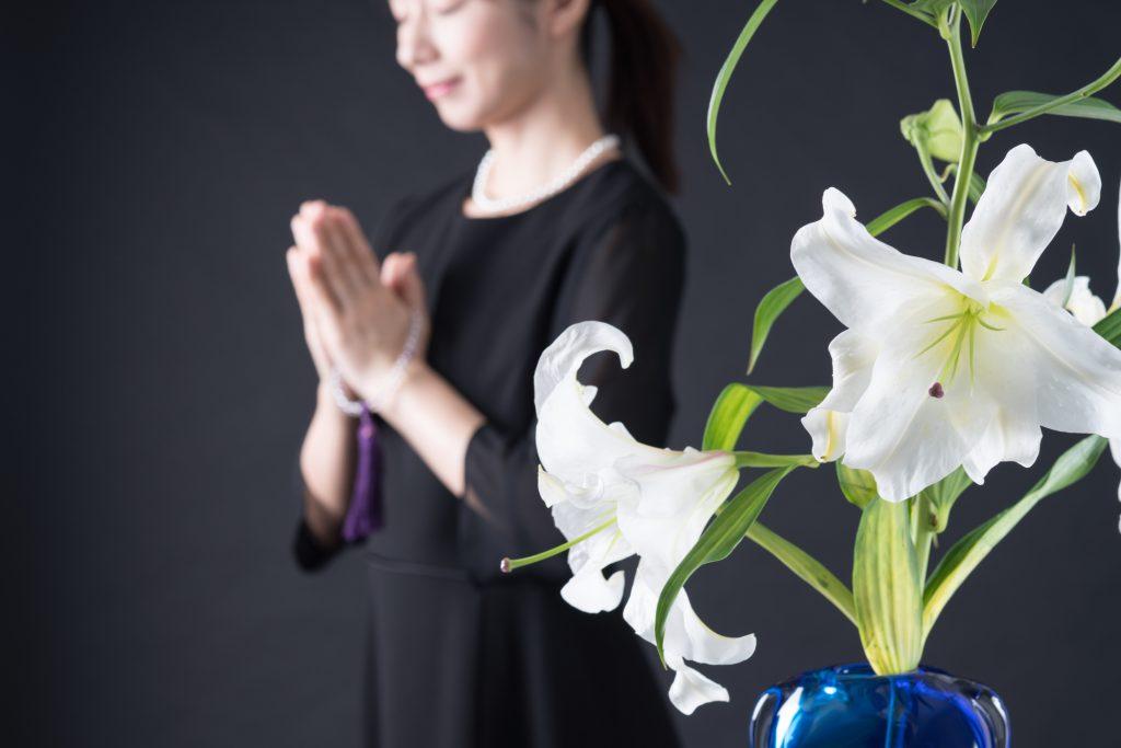 手を合わせる女性と百合の花