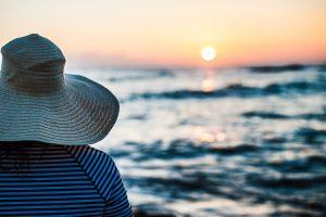 夕方の海を眺める女性の後ろ姿