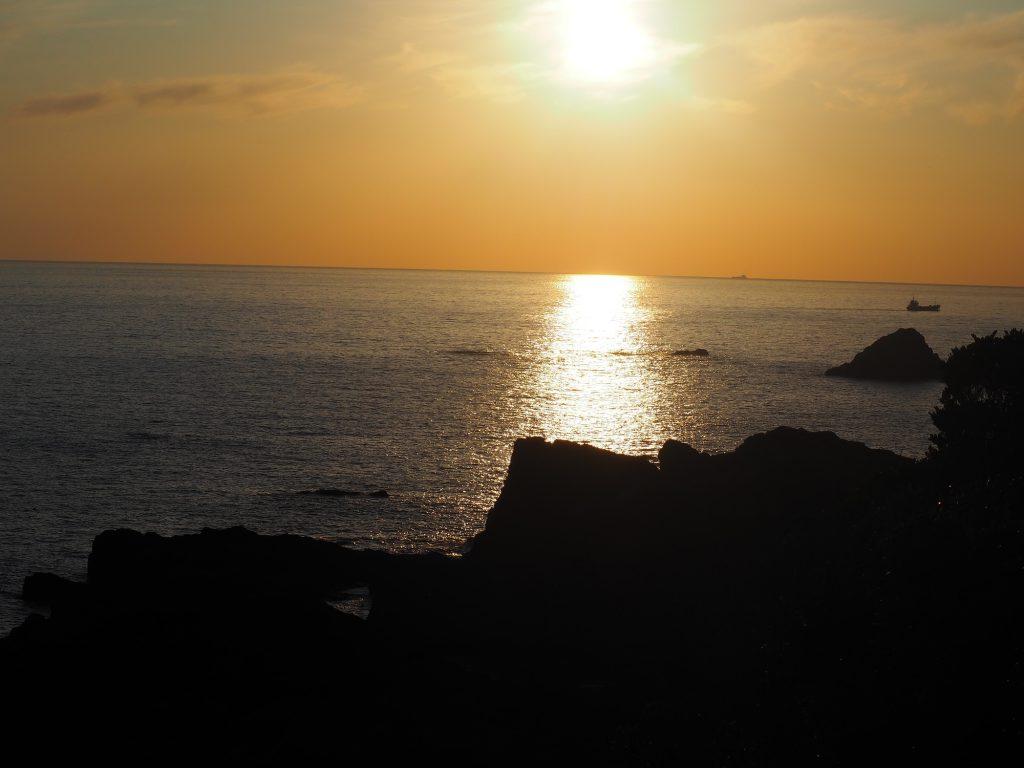 山の上から見る海と夕日