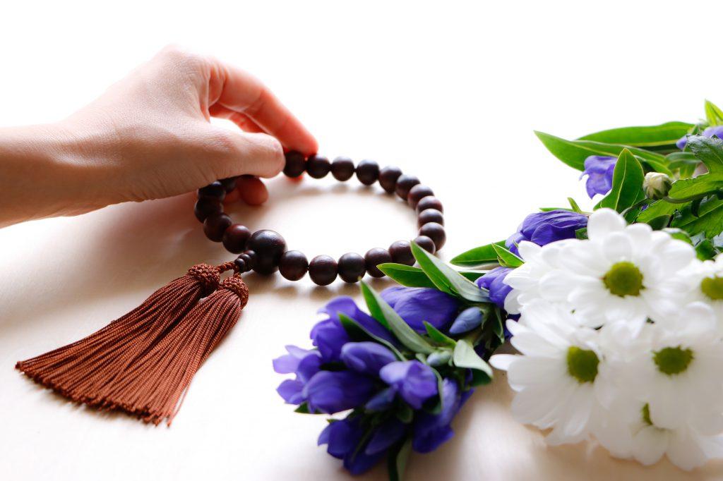 数珠を持つ手と切り花