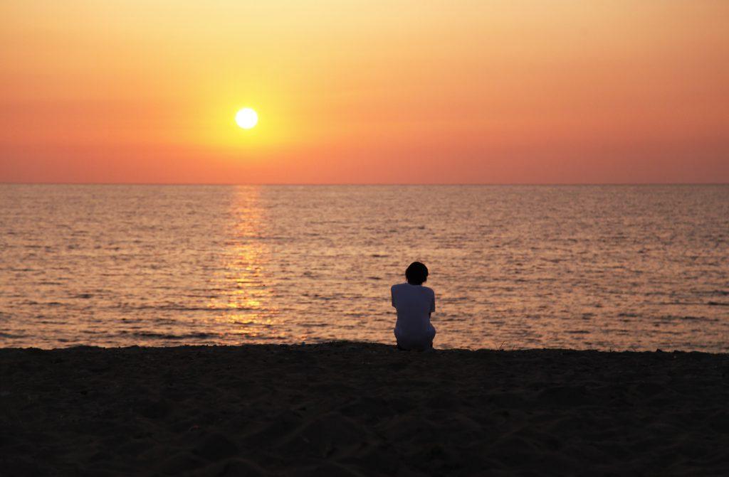 海に沈む夕日を見つめる後ろ姿