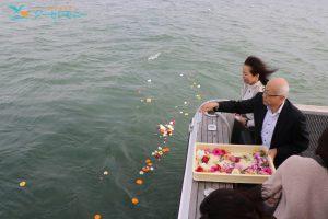 散骨セレモニーで東京湾に献花する男性と見守る家族