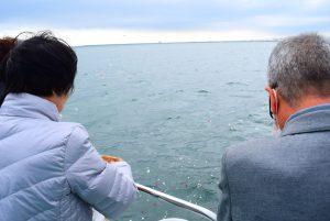 散骨セレモニーで東京湾に献花する高齢の男女