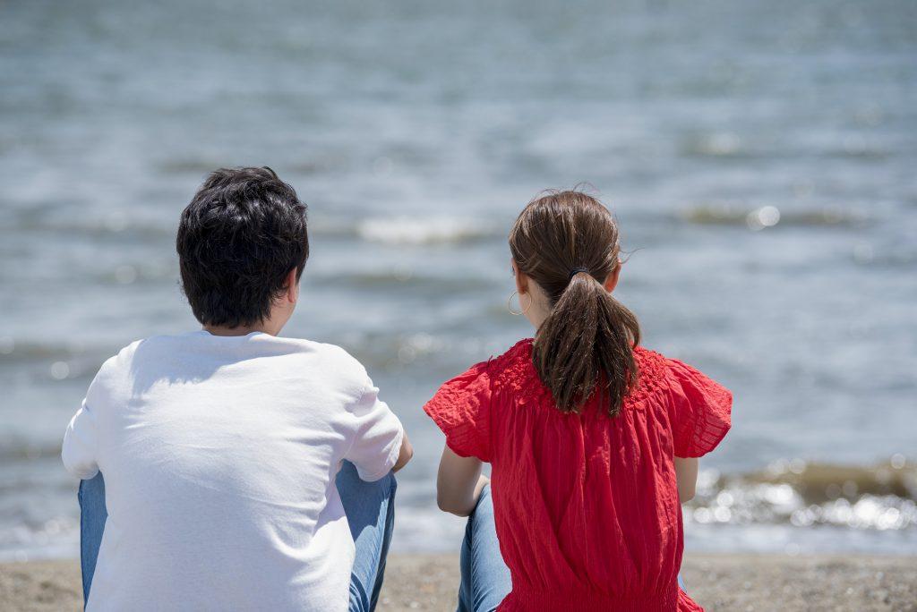 砂浜に座る男女の後ろ姿