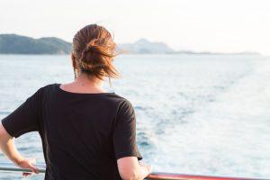 船から海を見つめる女性の後ろ姿