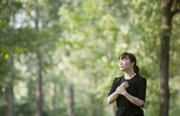 木々に囲まれた場所に立つ女性
