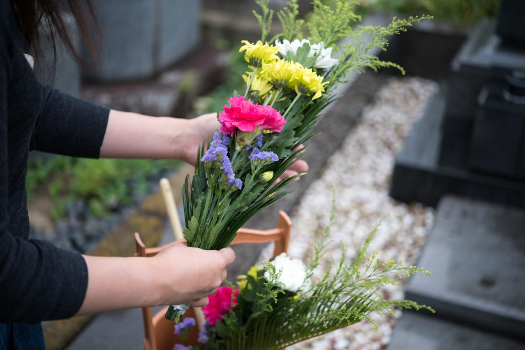 お墓に花を供える人