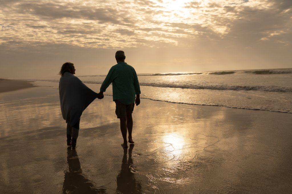 手をつないで波打ち際を歩く夫婦