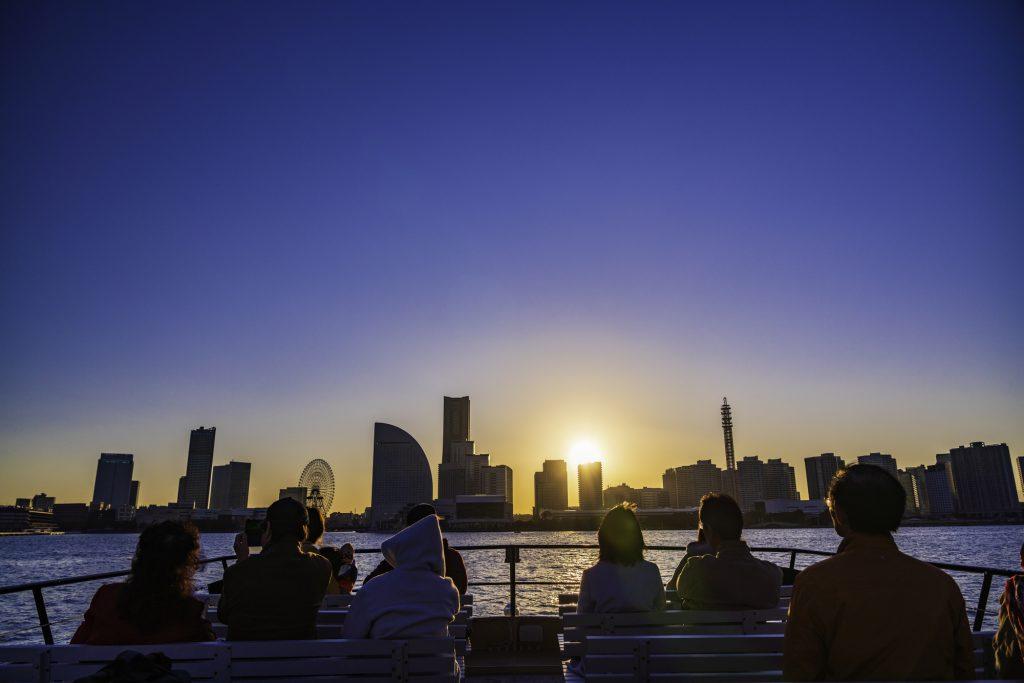 船のデッキに座り景色を眺める人たち