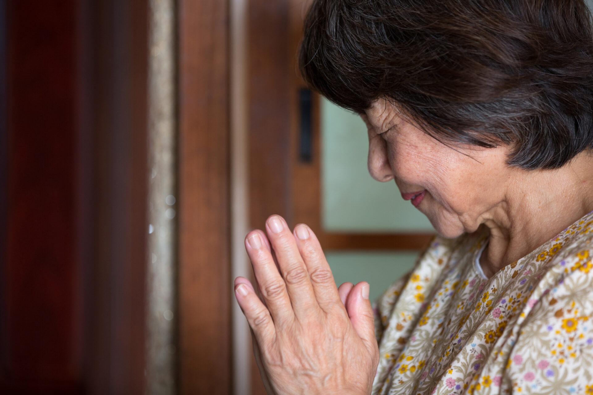 女性が手を合わせて黙祷する